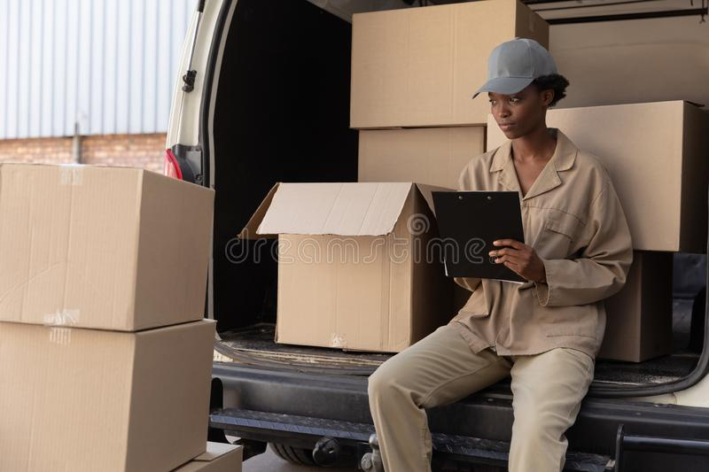 Delivery woman writing on clipboard near van outside the warehouse stock image
