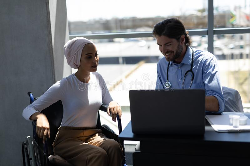 Disabled mixed-race woman and Caucasian male doctor interacting with each other royalty free stock images
