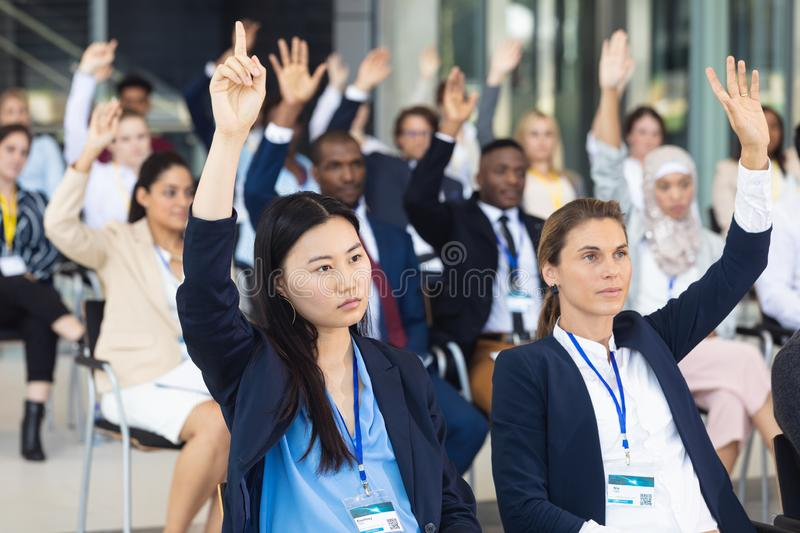 Business people asking question during speech in conference room. Front view of diverse business people asking question during speech in conference room stock image