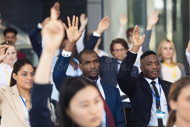 Diverse business people asking question during speech in conference room. Front view of diverse business people asking question during speech in conference room royalty free stock image