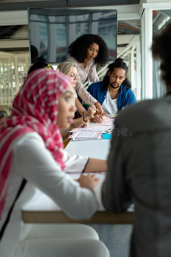Business people discussing together over documents at conference room in a modern office. Front view of diverse business people discussing together over stock photos