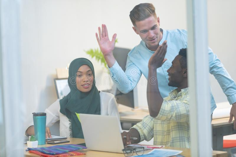 Business people giving high five while working together at desk in a modern office stock photography
