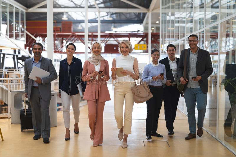 Business people looking at camera while walking in a modern office stock image