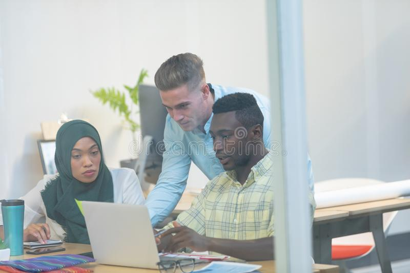 Business people working together on laptop at desk in a modern office stock photo