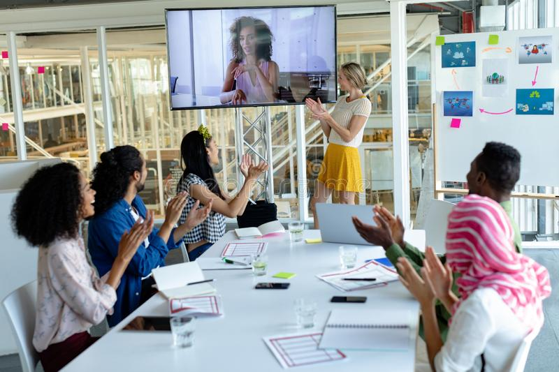 Business people applauding during video conference at conference room in a modern office. Front view of diverse happy  business people applauding during video royalty free stock photo