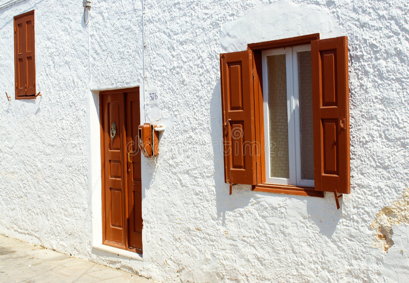 Front view of door and windows. On the street of ancient town Lindos. Rhodes. Greece stock photos