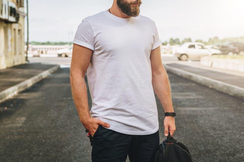 Front View El hombre milenario barbudo joven vestido en la camiseta blanca es soportes en la calle de la ciudad Mofa para arriba fotos de archivo