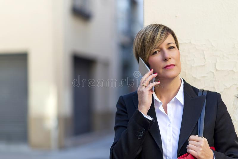 Front view of a elegant business woman standing and leaning on a street wall while using mobile phone and looking camera outdoors stock photos