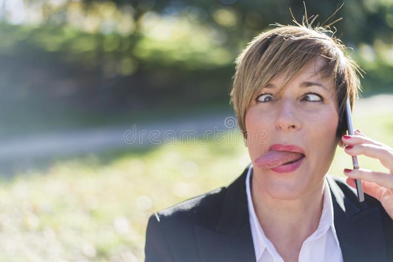 Front view of elegant smiling business woman sitting on a bench in a park while using a mobile phone showing her tongue outdoors royalty free stock photo