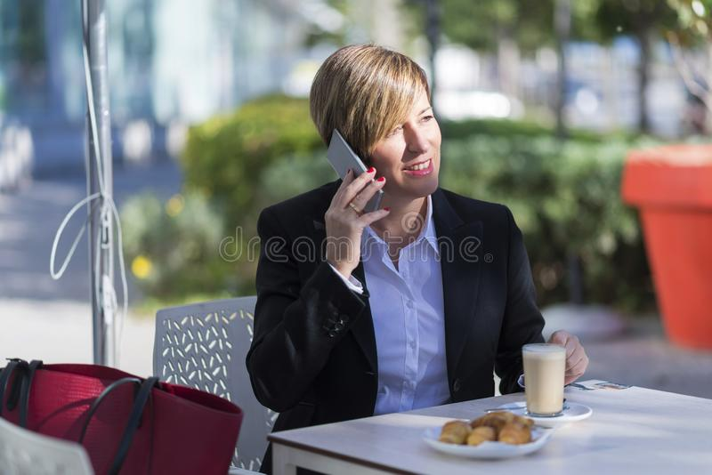 Front view of elegant smiling business woman sitting on a chair in a coffee shop while using a mobile phone enjoying the stock photos