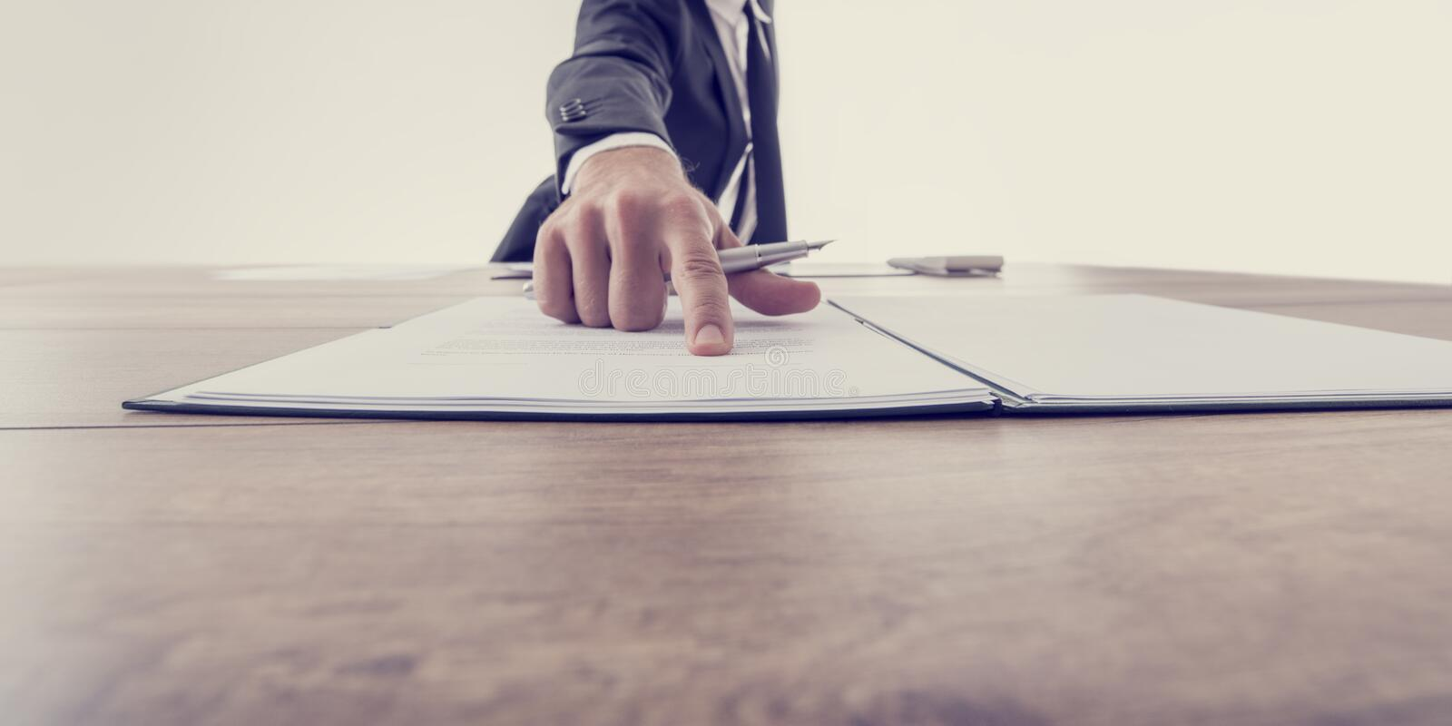 Front view of employer pointing to a contract. Where to sign, vintage effect toned image royalty free stock image
