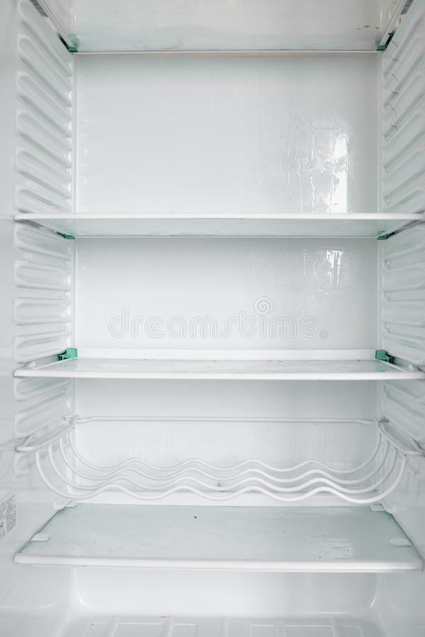 Front view of empty refrigerator staying at home. White modern freezer without food, vegetables and fruits in house. Electrical fridge with several shelves royalty free stock photography