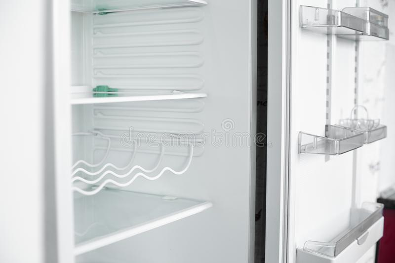 Front view of empty refrigerator staying at home. White modern freezer without food, vegetables and fruits in house. Electrical fridge with several shelves stock image