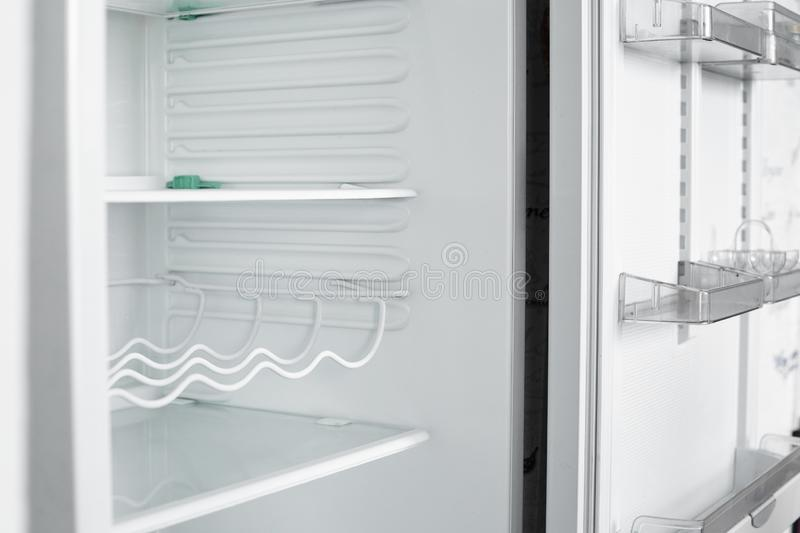 Front view of empty refrigerator staying at home. White modern freezer without food, vegetables and fruits in house. Electrical fridge with several shelves royalty free stock photo