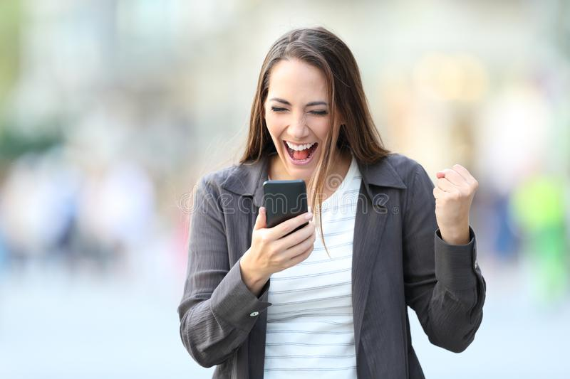 Front view of excited woman checking phone stock photography