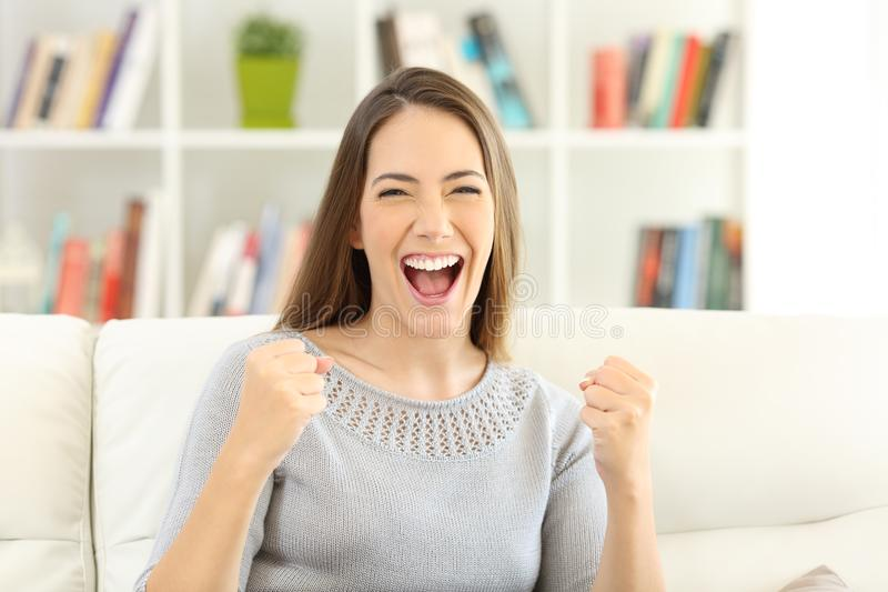 Front view of an excited woman looking at camera at home royalty free stock images