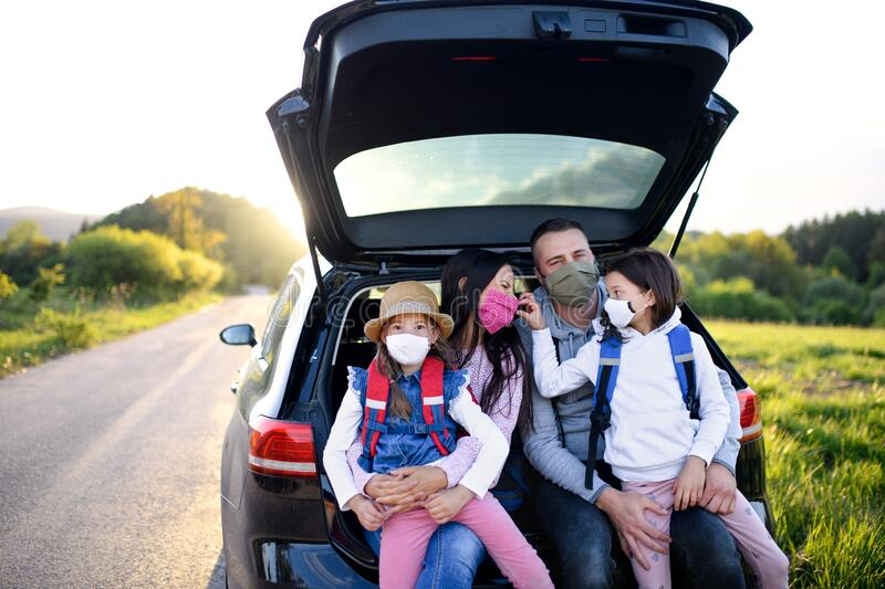Family with two small daughters on trip outdoors in nature, wearing face masks. stock image