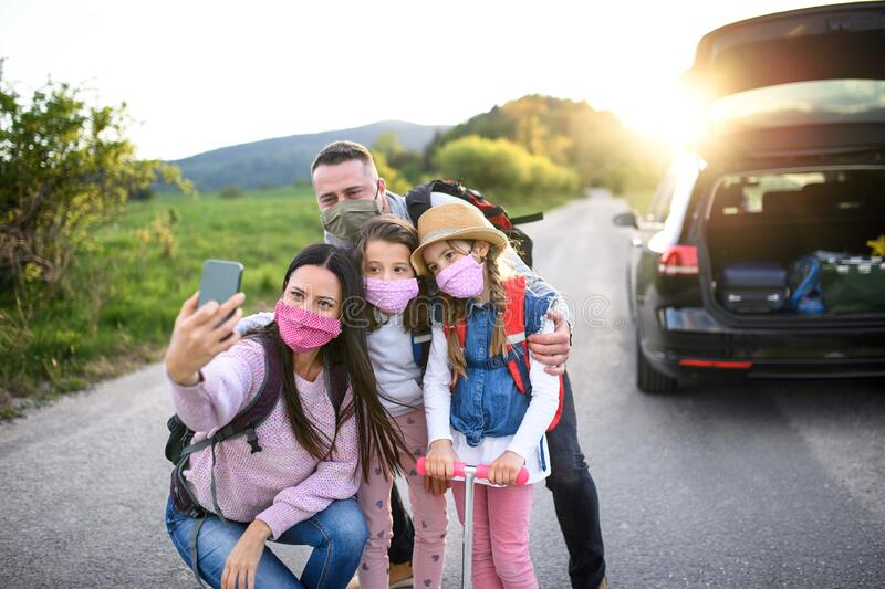 Family with two small daughters on trip outdoors in nature, wearing face masks. royalty free stock image