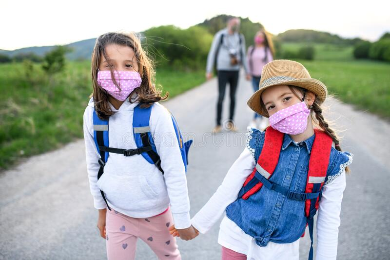 Family with two small daughters on trip outdoors in nature, wearing face masks. royalty free stock photo