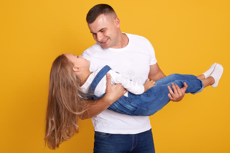 Front view of father holding little daugther wearing shirt and overalls in hands isolated over yellow studio background, handsome royalty free stock photos