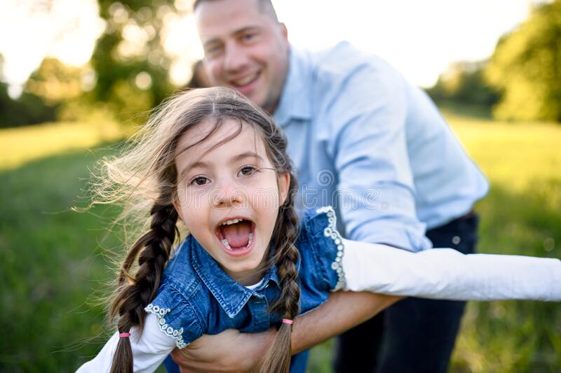 Father playing with small daughter outdoors in spring nature, having fun. stock photos