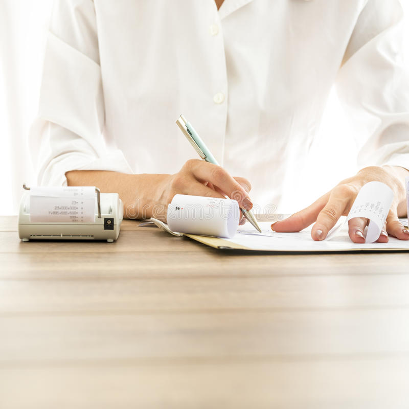 Front view of female bank employee writing something on receipts royalty free stock images