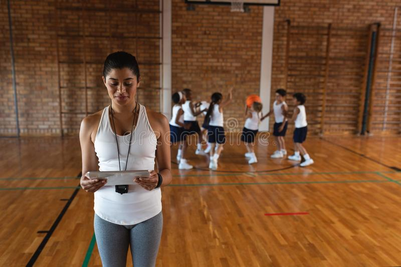 Front view of female basketball coach using digital tablet at basketball court stock photos