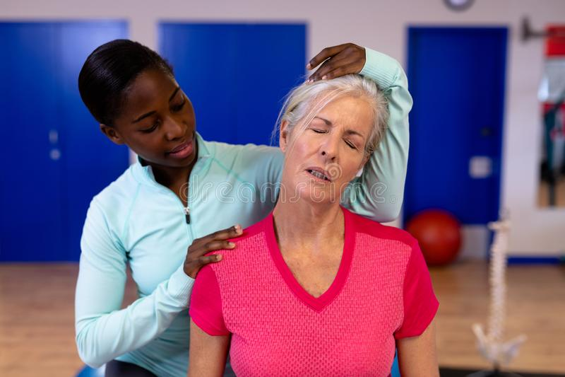 Female physiotherapist giving neck massage to active senior woman in sports center. Front view of female physiotherapist giving neck massage to active senior stock images