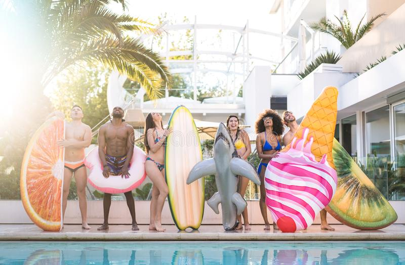 Front view of friends at swimming pool party with lilo airbed and swim wear - Youth vacation concept with happy guys and girls stock photo