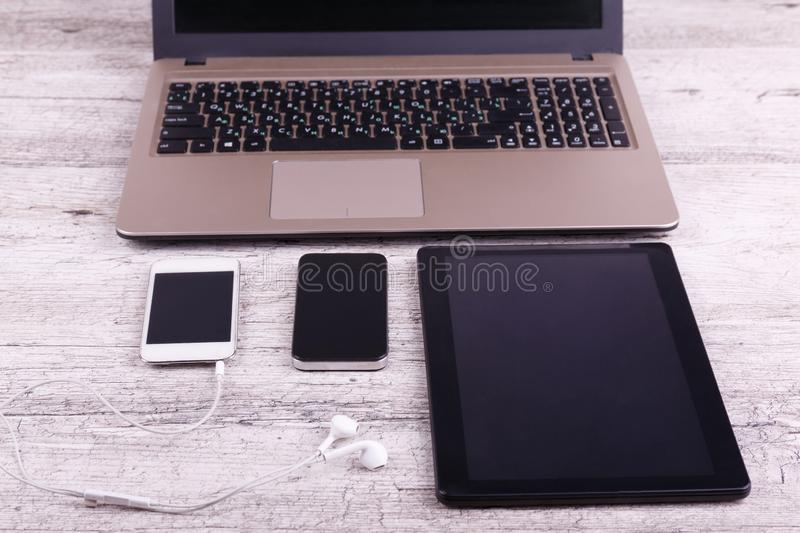 Front view, gray background, two mobile phones, a laptop and a tablet. royalty free stock photo
