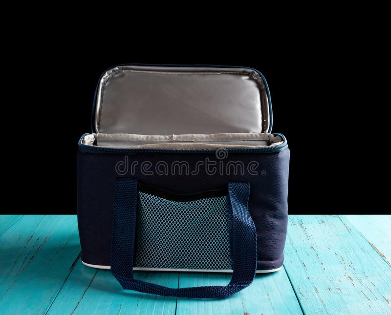 Front view grey and blue lunch pack carrier with the top opened on a wood table on black stock photos