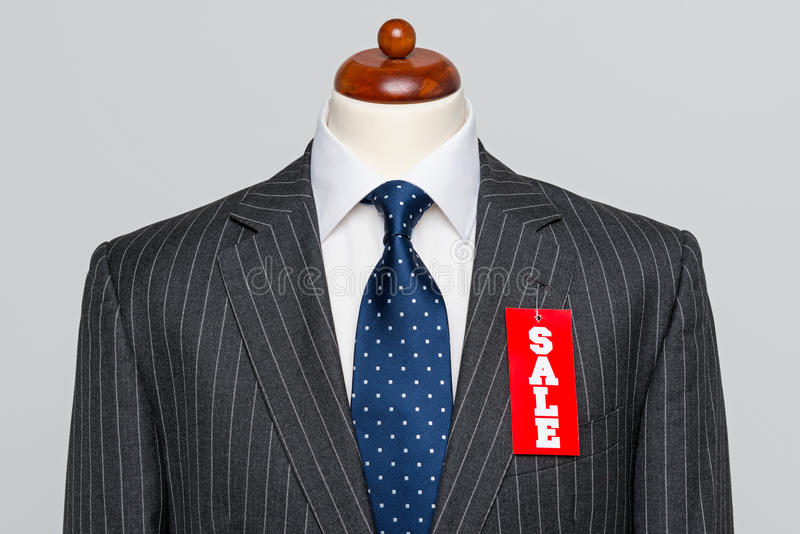 Front view Grey pinstripe suit Sale. Front view of a Mens grey wool pinstripe suit jacket with blue tie and white shirt on a tailors dummy, sale price tag royalty free stock images