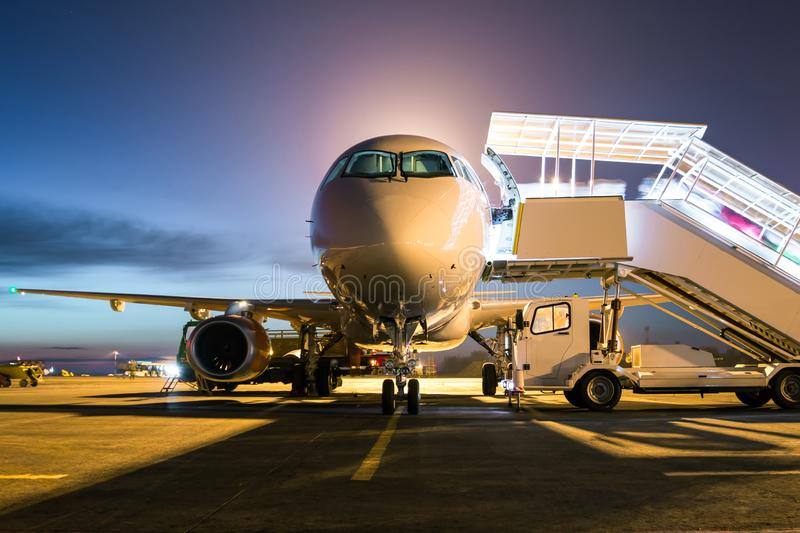 Front view ground handling of white passenger airplane with a boarding steps at the night airport apron stock image