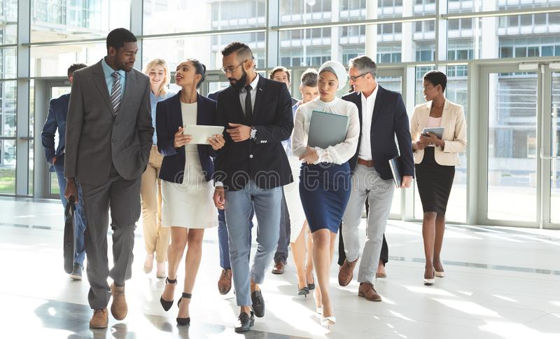 Front view of group of diverse business people walking together in lobby office. Front view of group of diverse business people walking together while discussing royalty free stock photos