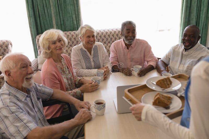 Group of senior people having black coffee in living room royalty free stock image