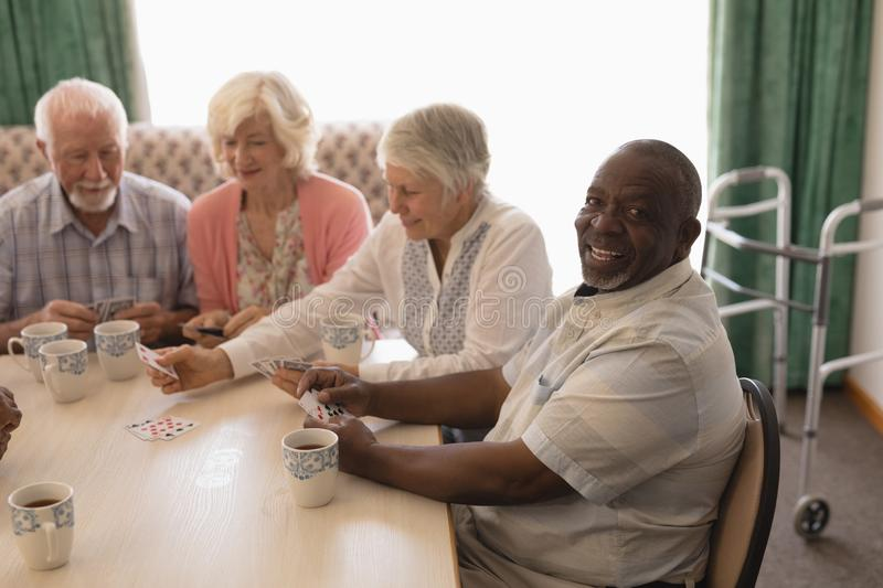 Group of senior people playing cards in living room stock images