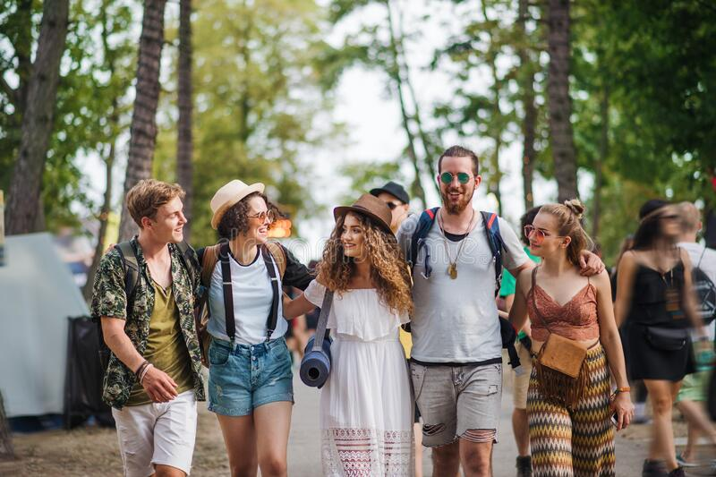 Front view of group of young friends with backpack walking at summer festival. royalty free stock images
