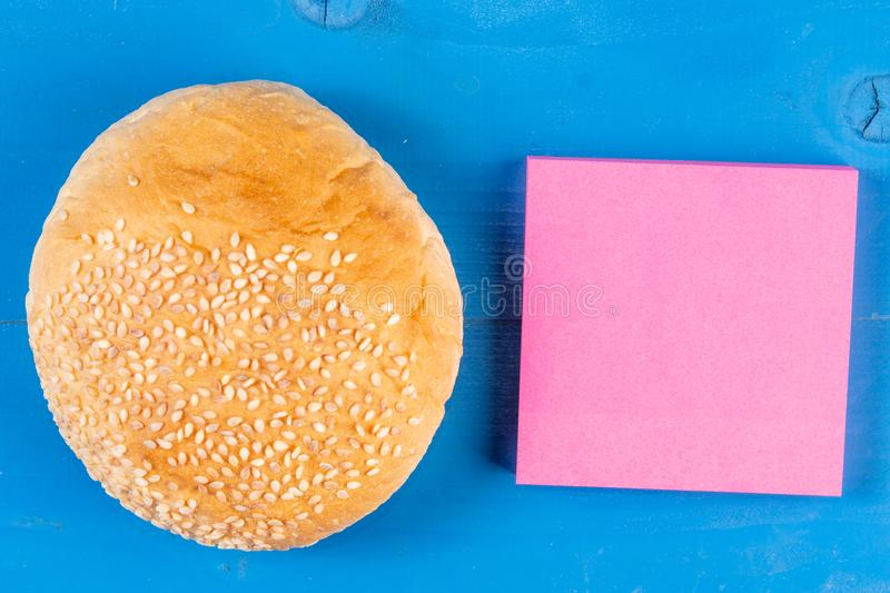 Front view hamburger roll colored sticky note wooden background. Meat bun paper sheet behind timber design. Remember royalty free stock images