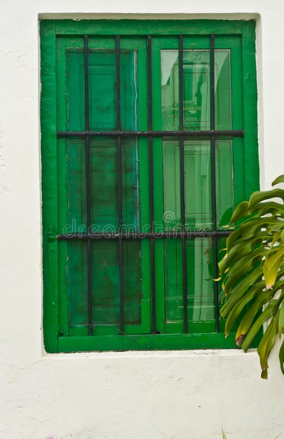 Green, shuttered, window with iron bares. Front view of a hand made, green, shuttered, window with iron bares to secure the above ground wine cellar and control royalty free stock photo
