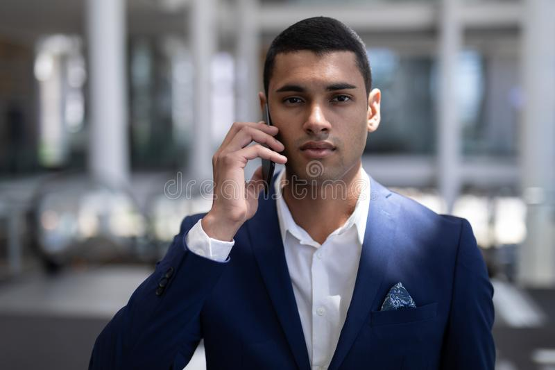Youmg mixed-race businessman looking at camera while using mobile phone in modern office stock photo