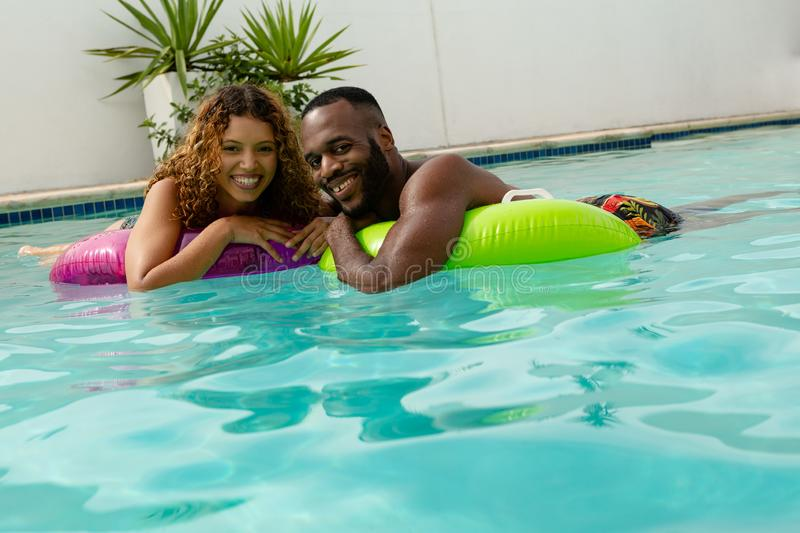 Couple floating on inflatable tube in swimming pool royalty free stock photo