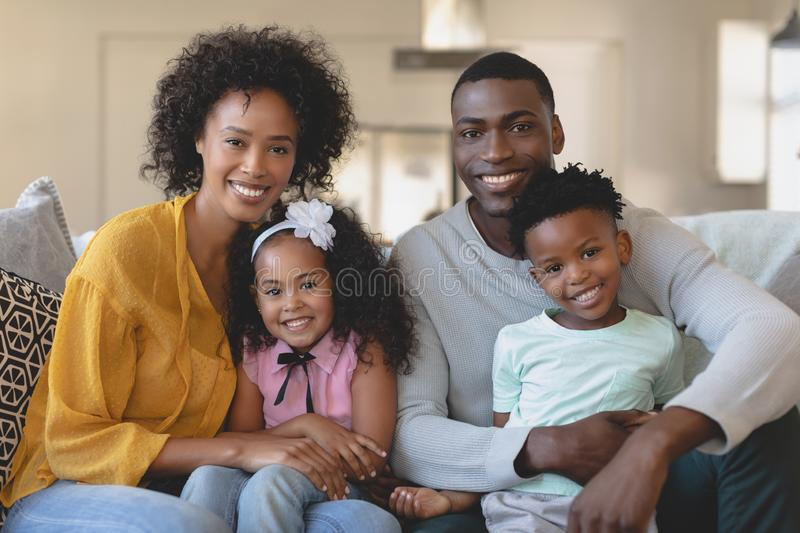 Happy African American family sitting on sofa and looking at stock photo