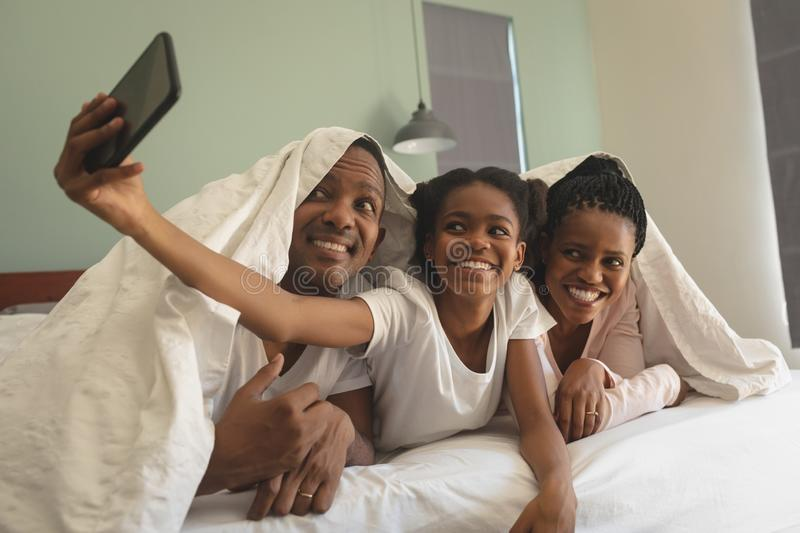 Happy African American family under blanket and taking selfie with mobile phone on bed royalty free stock photography