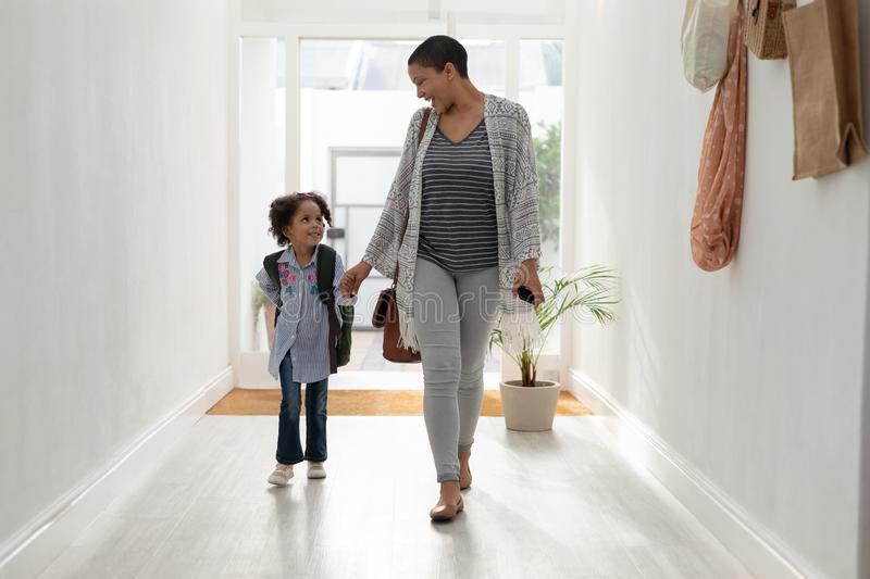 Girl with her mother walking together hand in hand near doorway at home royalty free stock image