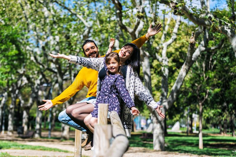 Front view of a happy arms raised family enjoying at park while looking camera and smiling in a sunny day stock image