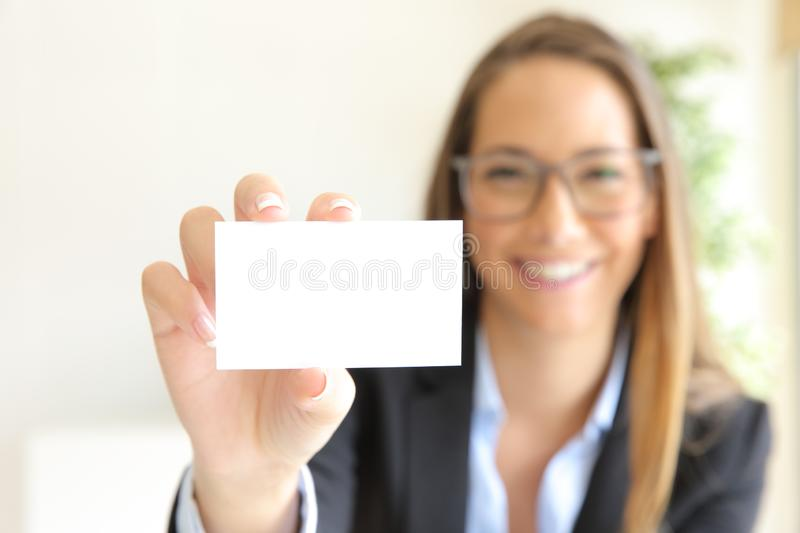 Happy businesswoman showing blank card at office stock photo