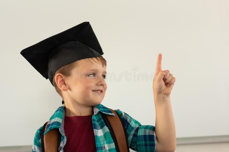 Happy boy in graduation cap pointing his finger in a classroom royalty free stock image