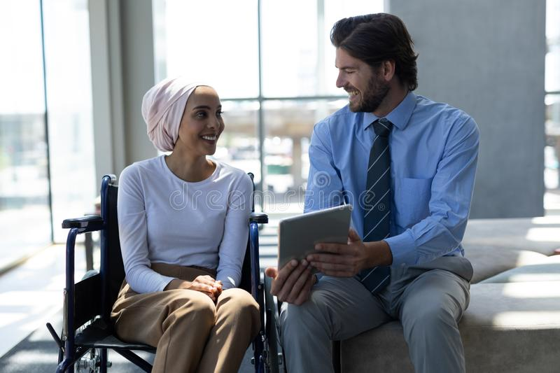 Happy disabled mixed-race female executive with Caucasian businessman discussing over digital tablet royalty free stock photos