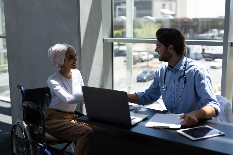 Disabled mixed-race woman shaking hands with Caucasian male doctor royalty free stock photo