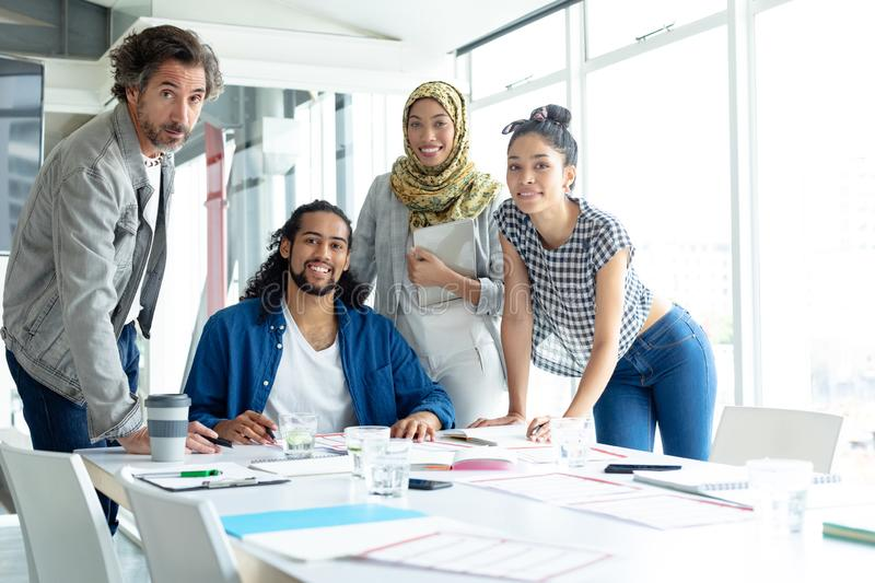 Business people looking at camera while working at conference room in a modern office. Front view of happy diverse business people looking at camera while stock images